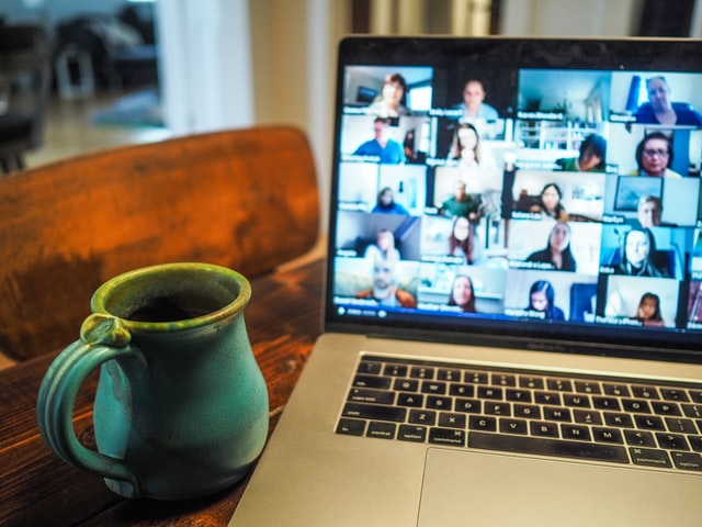 creative recruitment strategies - image of a laptop with a remote recruitment fair on it, alongside a mug