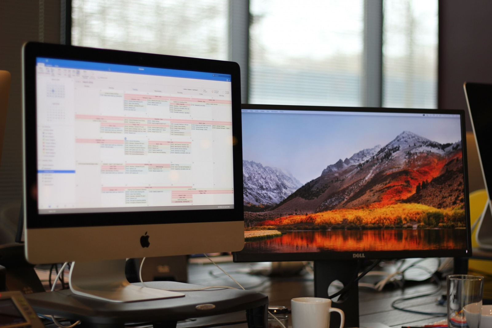A desk with two computer monitors, one showing a calendar.