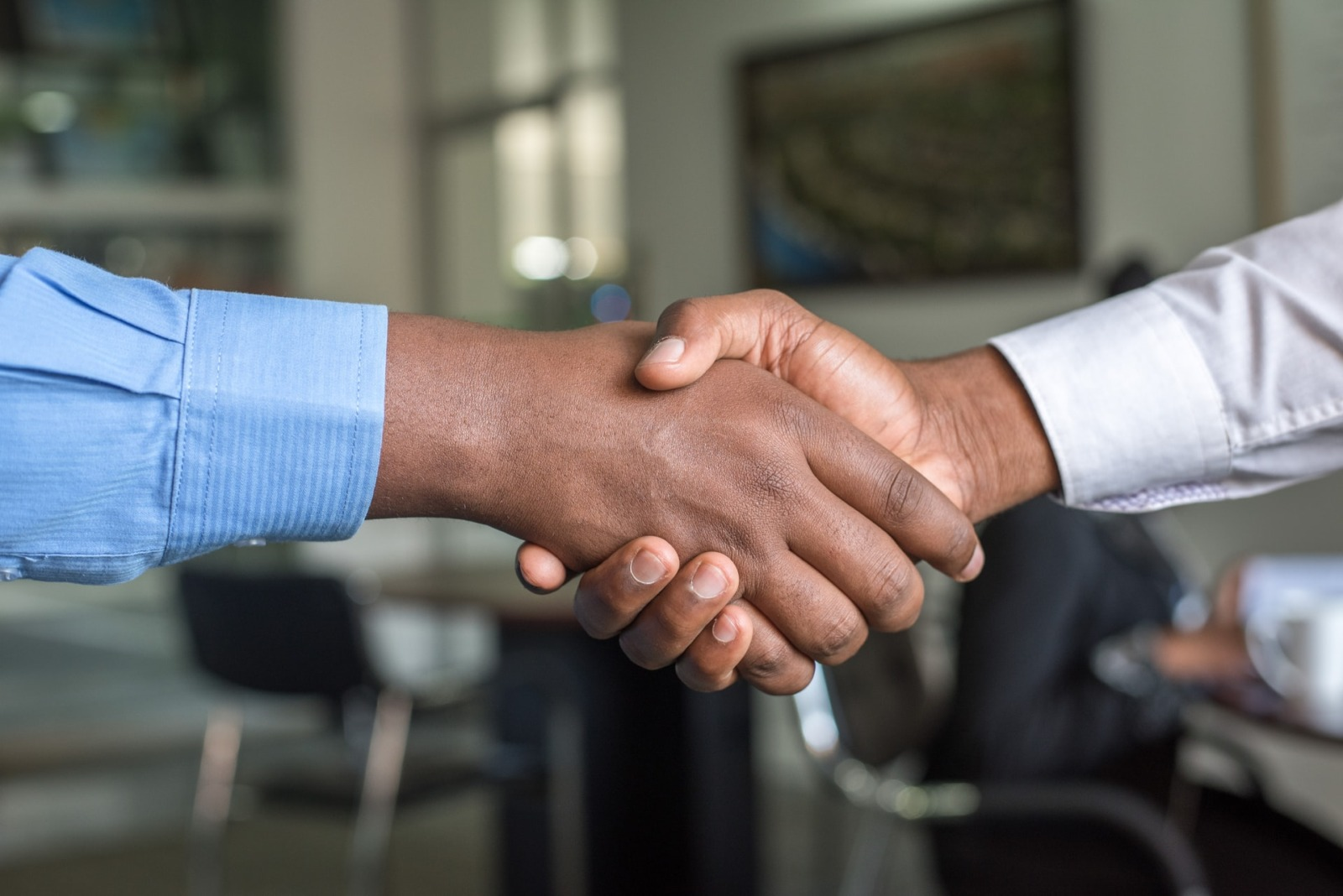 Two people shaking hands, indicating a that benchmark hiring works